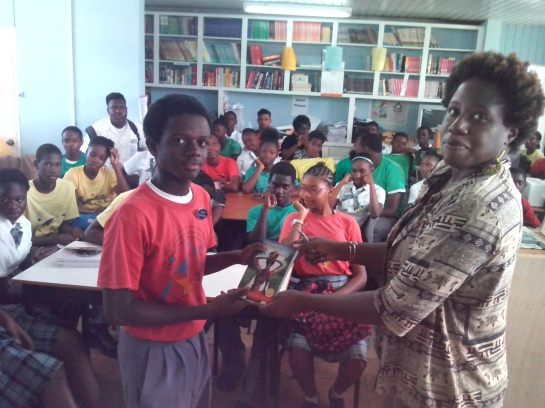 A student accepts my contribution of a copy of Musical Youth to the St. Mary's Secondary School library.