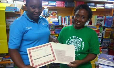 FLOW rep, Gavinia Michael, assisted with gift presentation to Wadadli Pen 2015 winner Margaret Irish (right). Photo by Glen Toussaint/Best of Books.