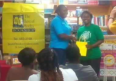 Gavinia Michael of FLOW presents the cable company's gift of a EC$500 gift certificate for books at the Best of Books to winner Margaret Irish. Photo by Barbara Arrindell/Best of Books.